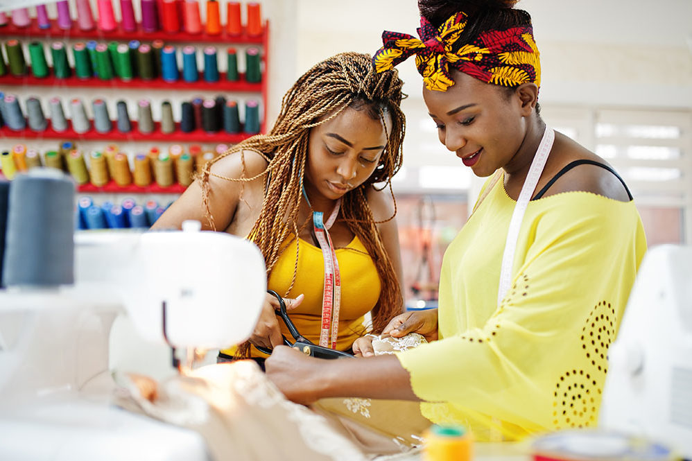 Two african dressmaker woman sews clothes on sewing machine and