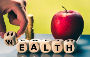 """Financial Wellness - Hand is turning a dice and changes the word """"Health"""" to """"Wealth"""""""
