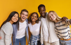 Life Skills - Friendly international students taking selfie over yellow background